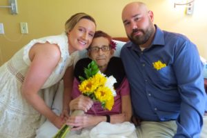 Newlyweds Spencer and Joe Newton pose with bride's mother a patient at Care Dimensions' Kaplan Family Hospice House
